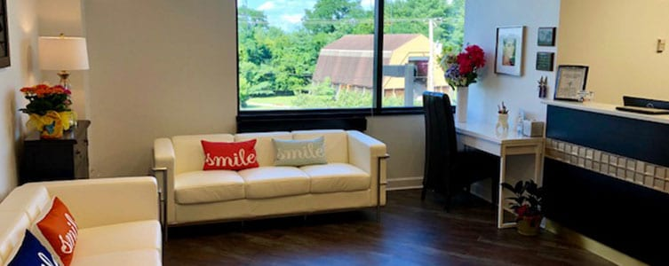 lobby at dentist office with white couches and pillows with the word smile on them