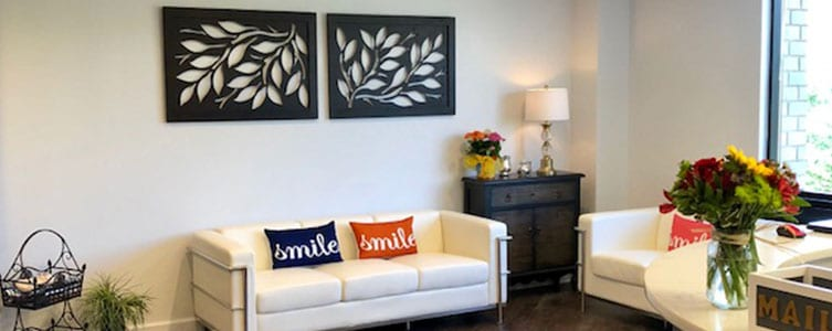 lobby at dentist office with white couch, colorful pillows