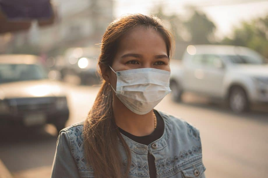 woman walking on sidewalk with hair in ponytail wearing a surgical mask